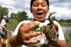 Boy with frog jumping out of container