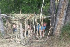 Boys hiding under shelter smiling