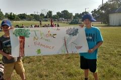 Mud Mucking-Boys holding sign