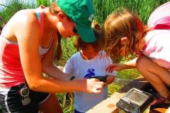 Mud Mucking kids and instructor examining net