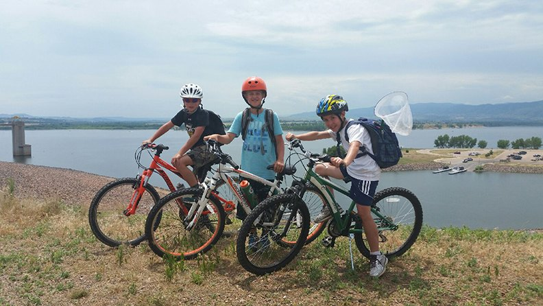Three boys bike along the Platte River during their time at Thorne Summer Camp